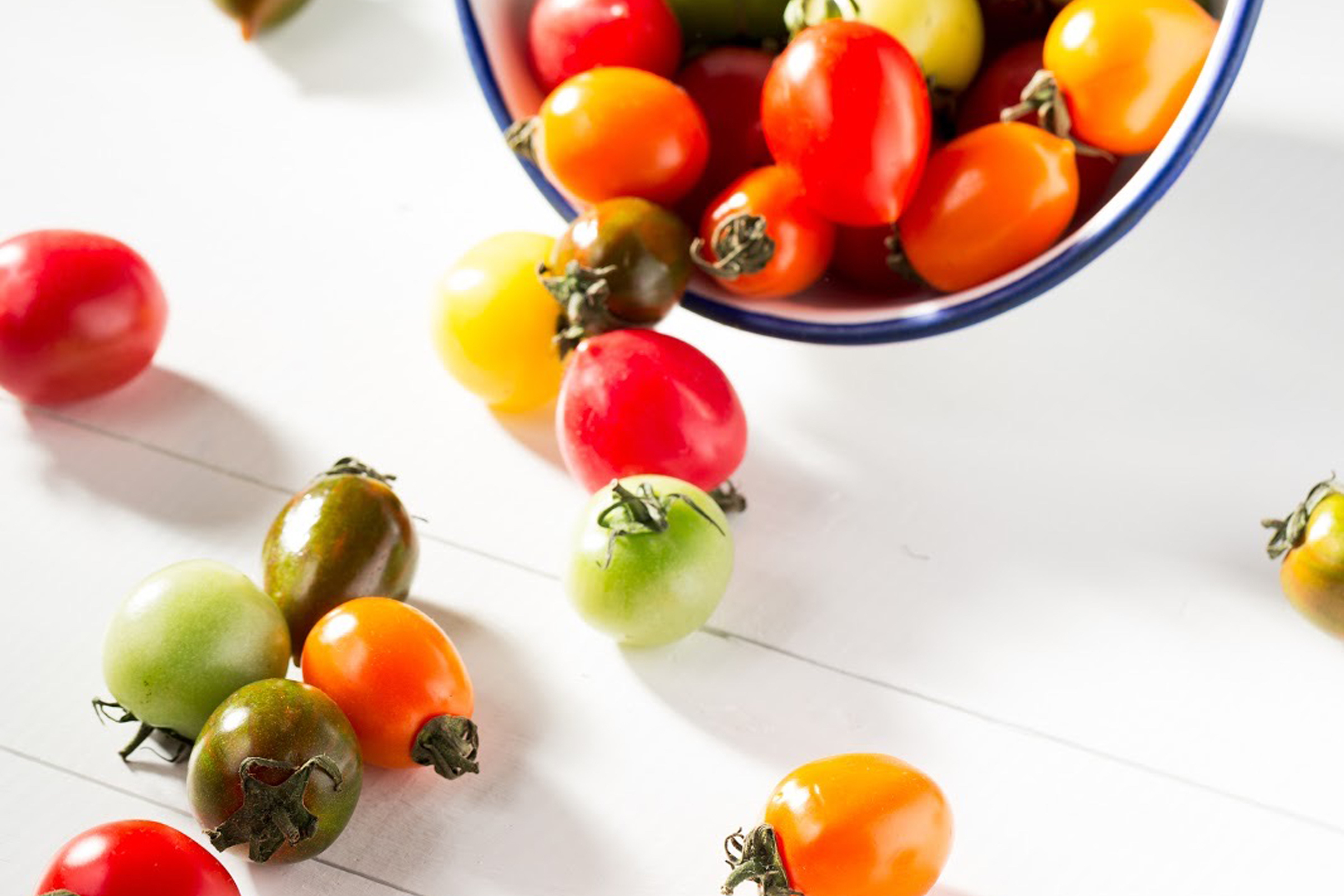 Bowl of fresh multi-colored cherry tomatoes spilling out onto countertop