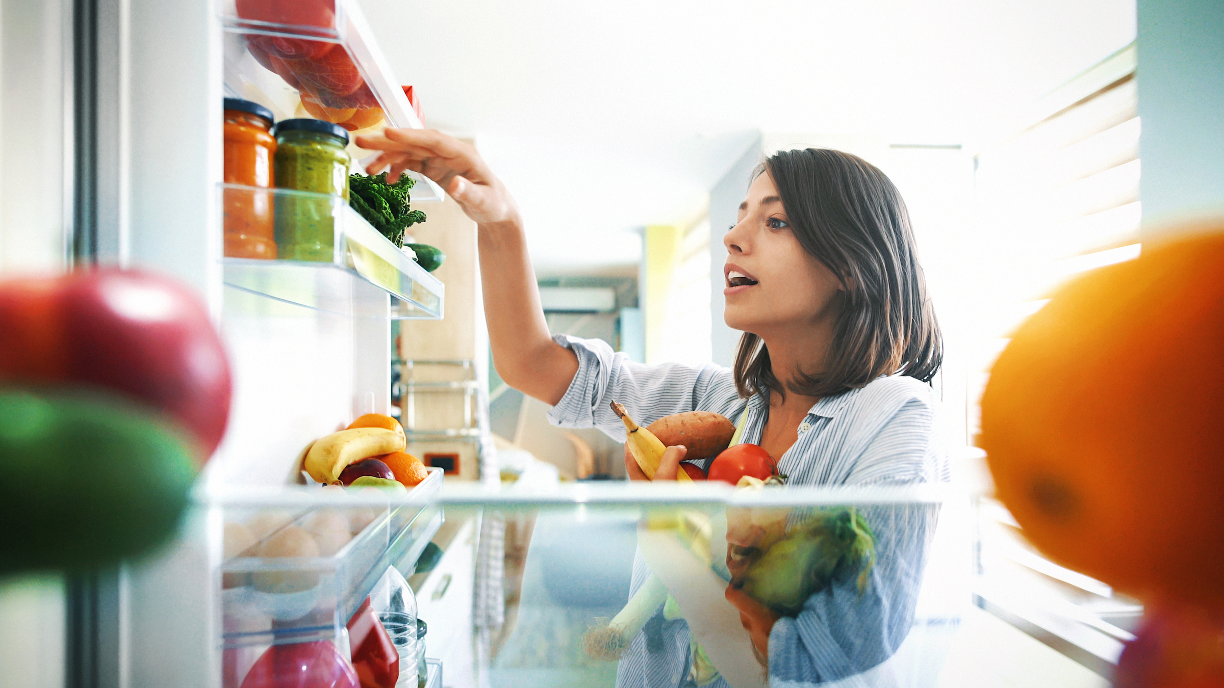 Woman retrieving colorful fruits and vegetables from refrigerator