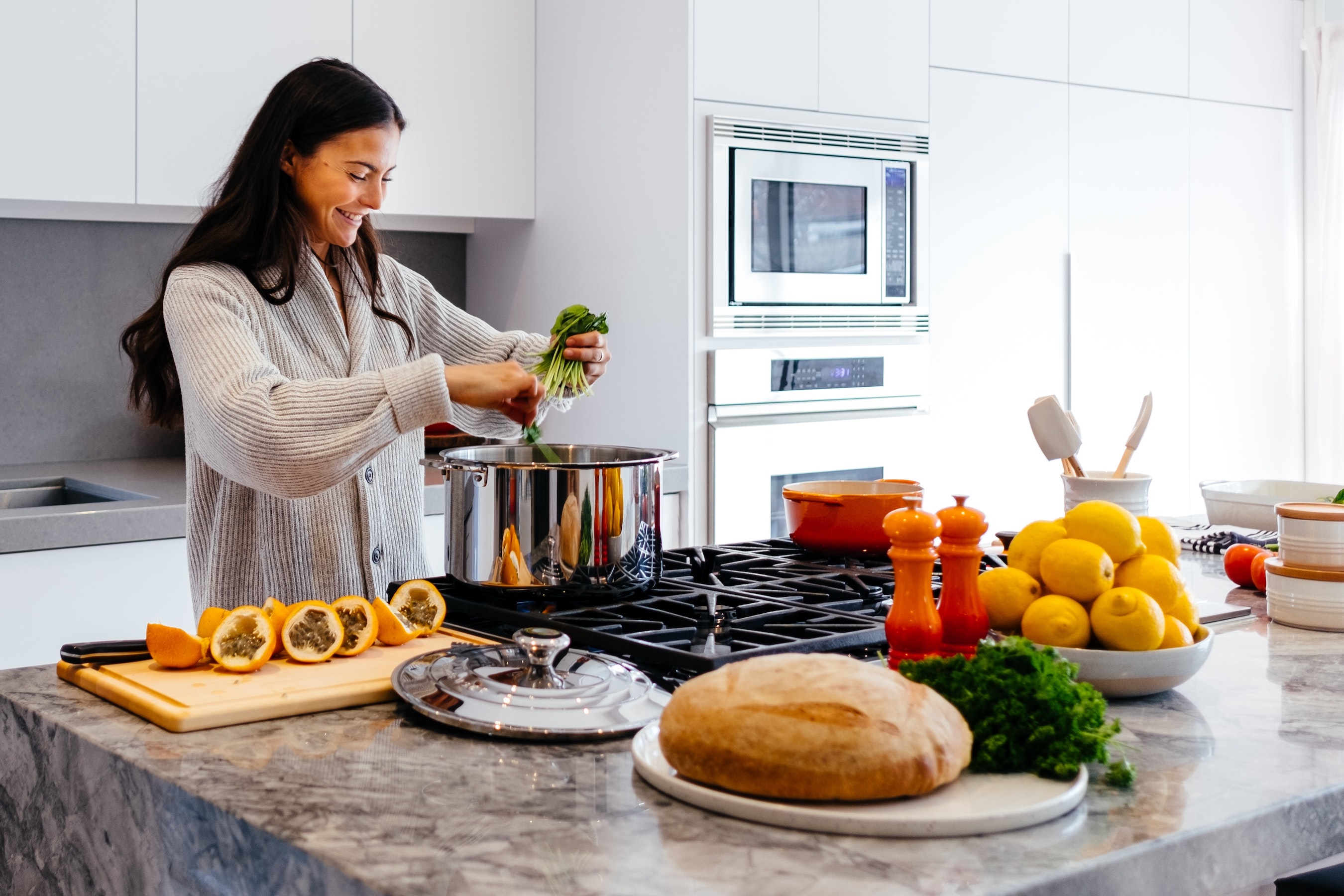 In a bright kitchen with marble countertops, a smiling caucasian woman with dark brown hair adds fresh greens to stockpot