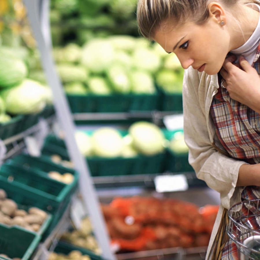 Woman looking at baskets of vegetables in supermarket