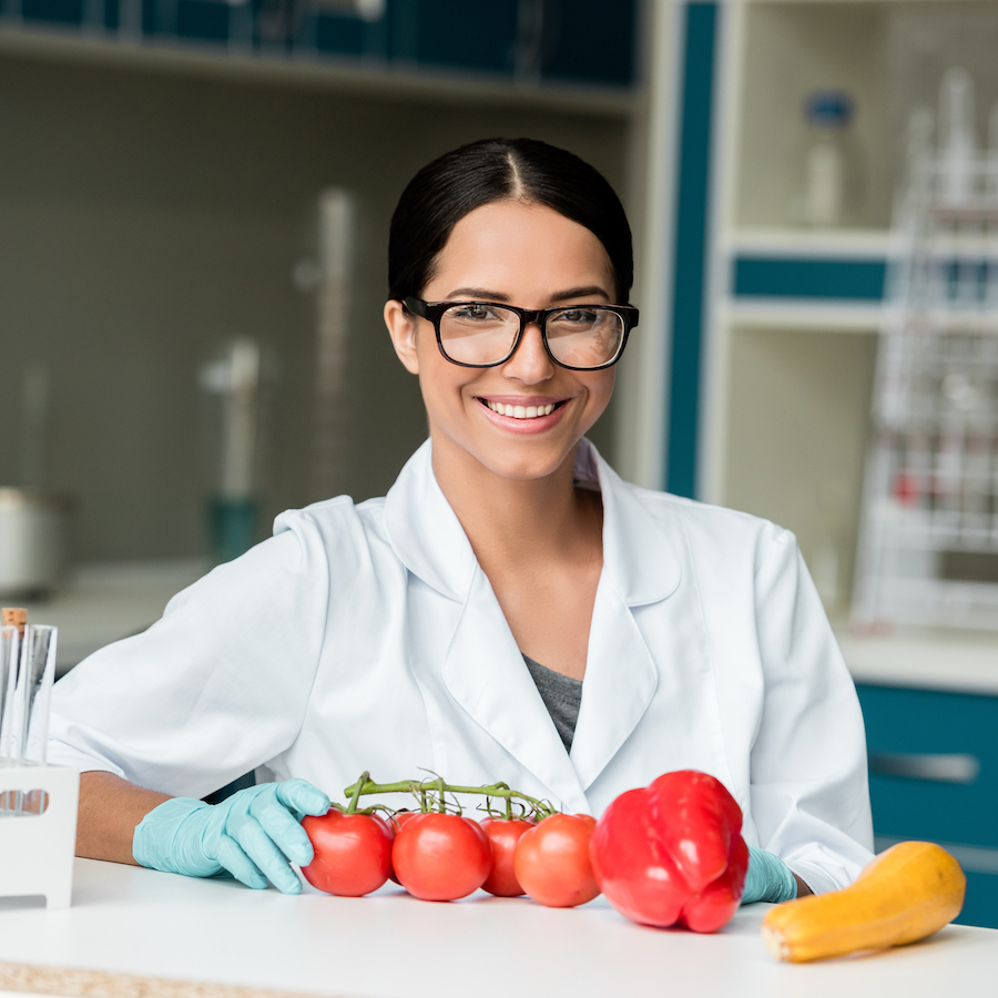 Woman scientist in lab setting with fresh veggies