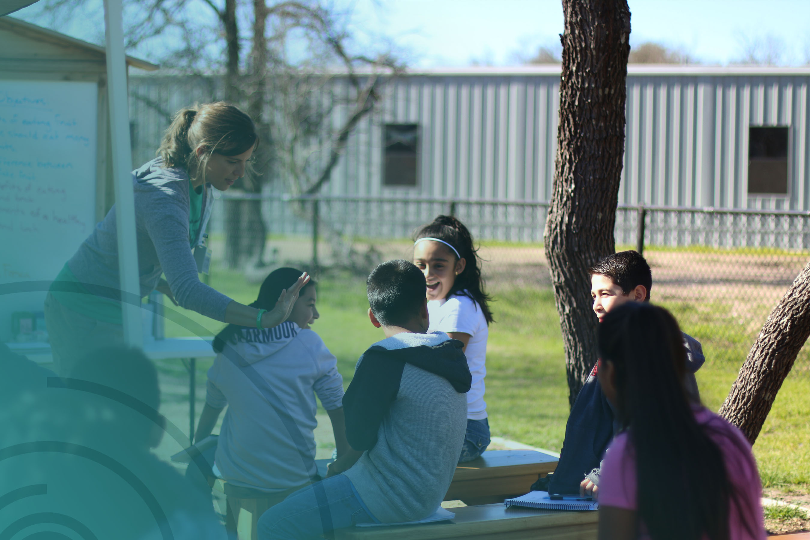 Nutrition and Garden Instructor high fiving students in outdoors classroom for TX Sprouts