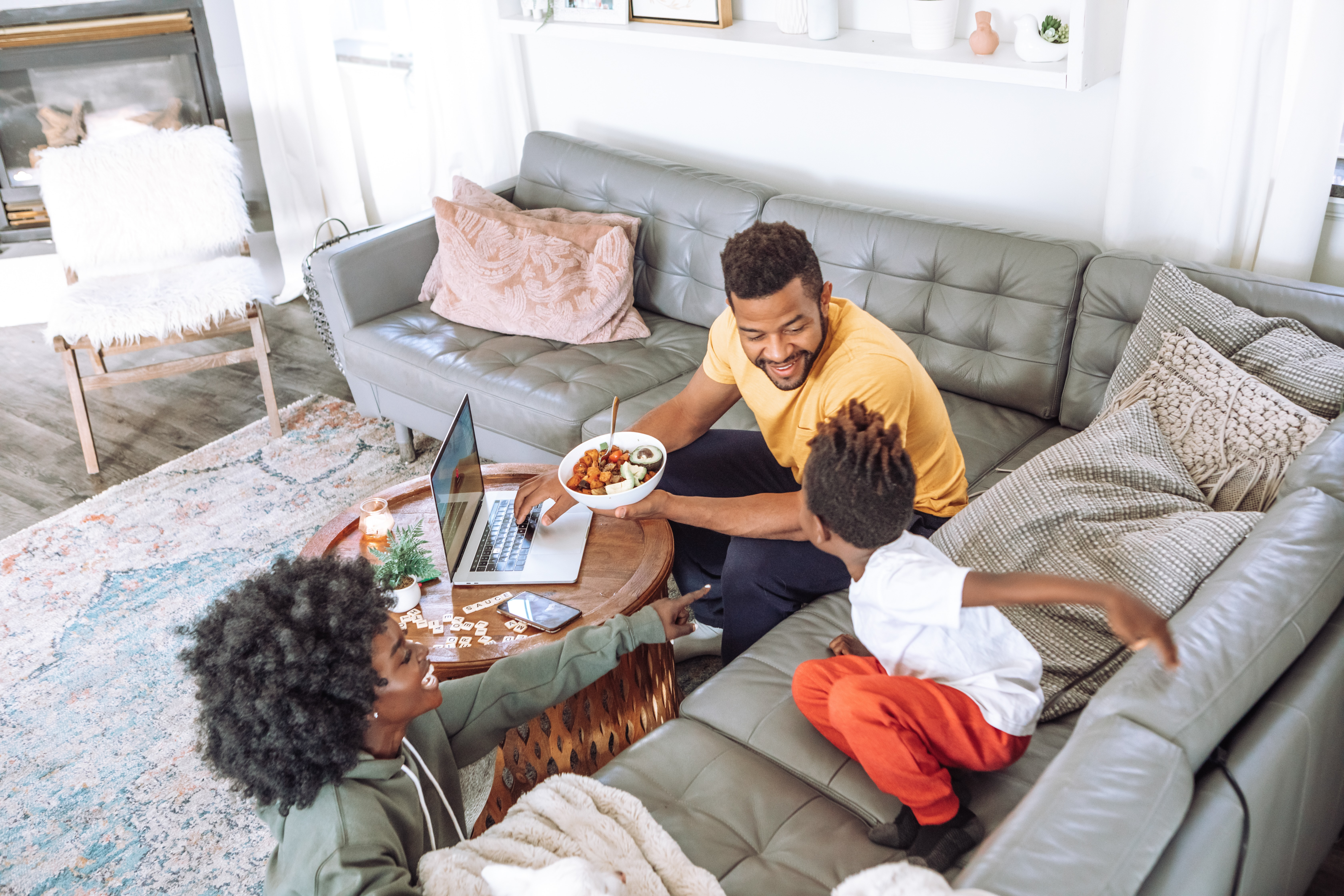 Three Black people sitting in a living room. One of the people is a child crouched on a couch. The two older people are engaging with the child.