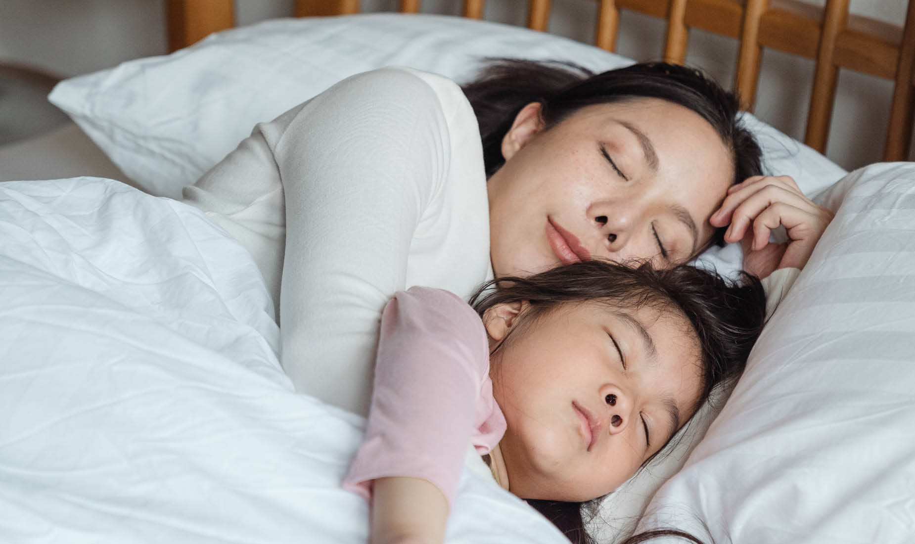 A mother and daughter of East Asian descent cuddling in bed looking contented.